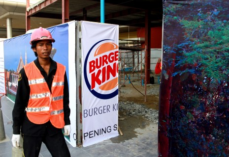 A worker stands beside an advertisement for Burger King at the Phnom Penh International Airport on Thursday. (Siv Channa)