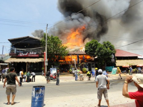 A fire engulfs a guesthouse along Serendipity Road in Sihanoukville on Sunday. A fleet of fire trucks struggled to extinguish the blaze, which destroyed four businesses, due to a severe water shortage in the area. (Hok Ly)