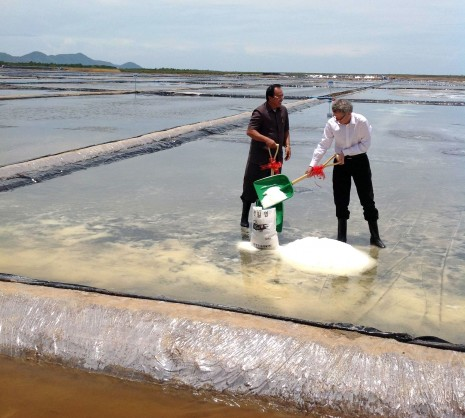 Bun Bariang, left, co-executive director of the Salt Association of Kampot, and Peter Bird, non-executive director of InfraCo Asia, shovel sea salt into a bag on Saturday at the inauguration of a new farm in Kampot province. (Simon Lewis/The Cambodia Daily)