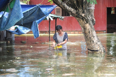 Aresident in Phnom Penh's Khva village wades through water near her home on Wednesday. (Simon Henderson/ The Cambodia Daily)