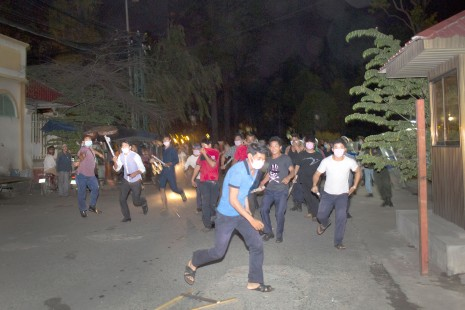 A civilian mob flanked by riot police and armed with Tasers, slingshots and sticks chase after Boeng Kak activists and journalists near Wat Phnom on Sunday night.