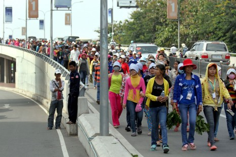 Protesting for an increase to their monthly minimum wage, garment factory workers march over the Russian Boulevard overpass Thursday morning, en route to join demonstrations at Phnom Penh's Freedom Park. (Siv Channa)