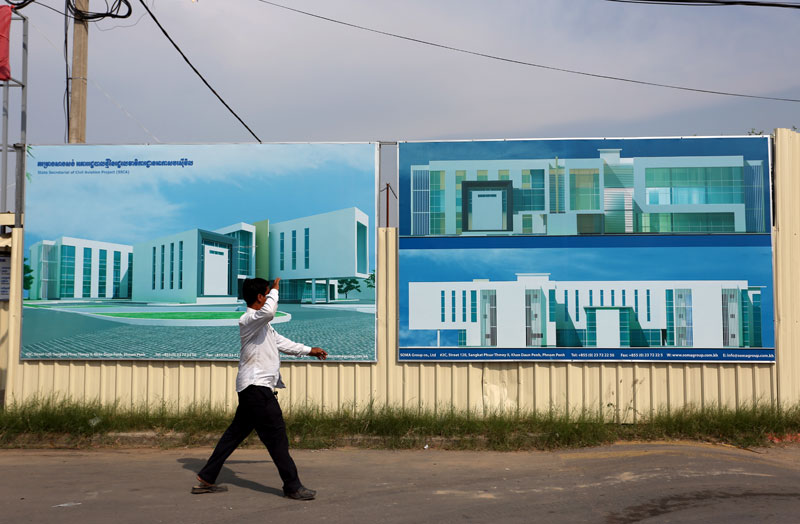 A man walks past the future site of the State Secretariat of Civil Aviation adjacent to the international airport on Russian Boulevard. (Siv Channa)
