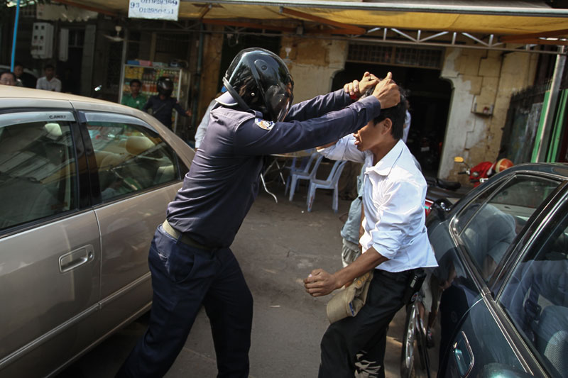 A Daun Penh district security guard prepares to knee a man in the face Monday on a street adjacent to Phnom Penh's Freedom Park. (Ishikawa Masayori)