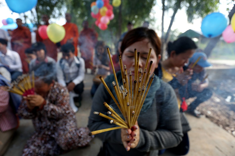 A supporter lights incense Wednesday in front of Prey Sar prison in Phnom Penh, where 21 garment workers and labor activists were transferred ahead of their trials on Friday. (Siv Channa)