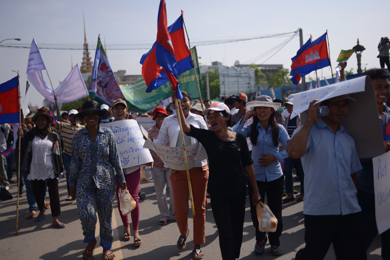 Union members retreat after being pushed back from the National Assembly by police in Phnom Penh on Thursday morning. About 200 people had gathered near the barricaded parliament building on International Workers' Day, holding signs calling for better working conditions, independent courts and more pay. (Lauren Crothers/The Cambodia Daily)