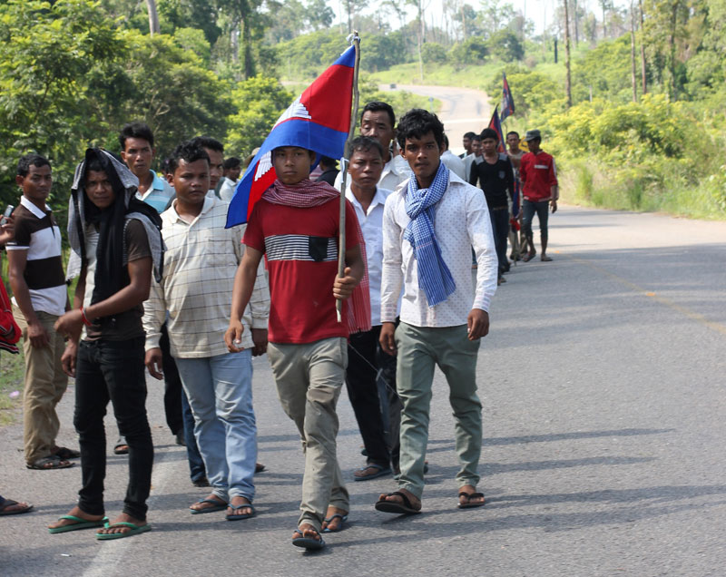 A group of men wait Sunday morning alongside a roadblock on Road 67, where CNRP leaders were supposed to travel on their way to Oddar Meanchey province's Anlong Veng district. (Alex Willemyns/The Cambodia Daily)