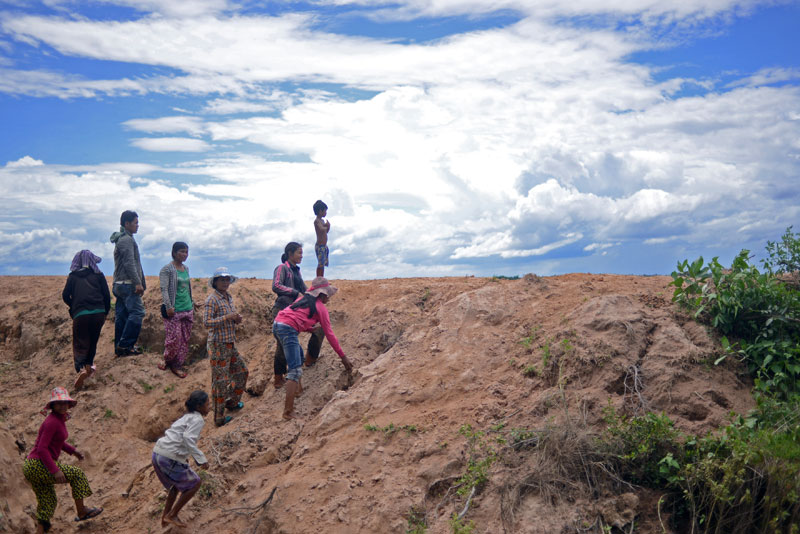 Lor Peang villagers clamber up the bank of a creek that demarcates the boundary of a disputed 145-hectare plot of land in Kompong Chhnang province on Monday, which they say the KDC company illegally grabbed from them in 2002. (Lauren Crothers/The Cambodia Daily)