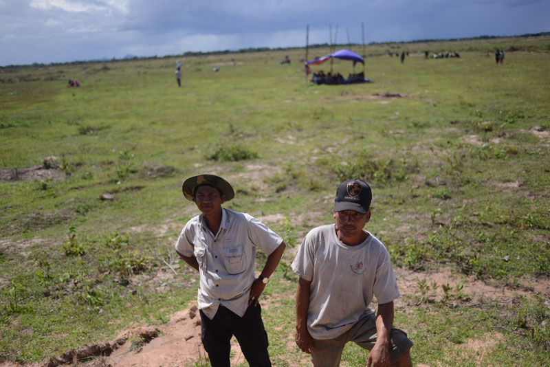 KDC workers waited for instructions from their superiors to continue clearing land and flattening the bank to erect a wall around the disputed site. (Lauren Crothers/The Cambodia Daily)
