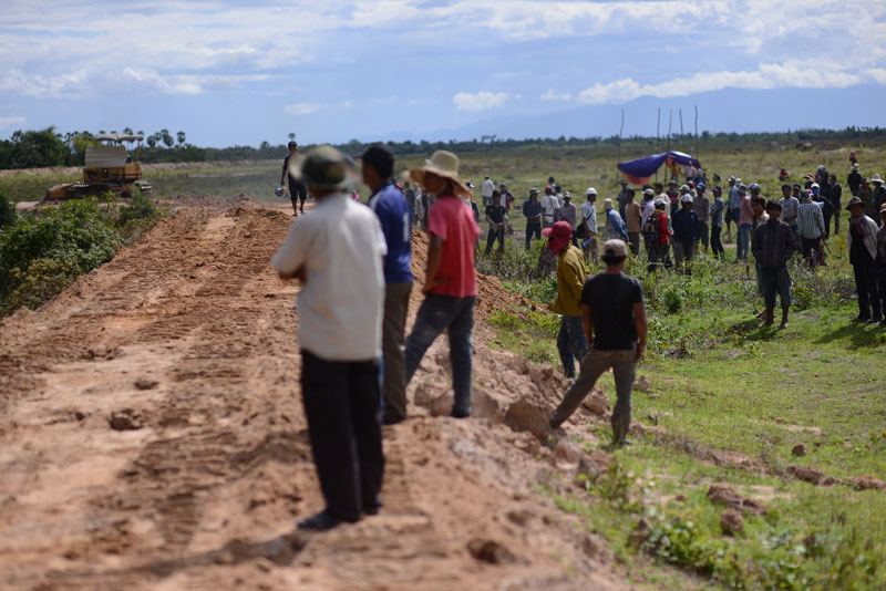 By about 3 p.m., a tractor began moving earth and flattening the bank that villagers had earlier climbed up. More than an hour later, villagers and workers clashed again. (Lauren Crothers/The Cambodia Daily)
