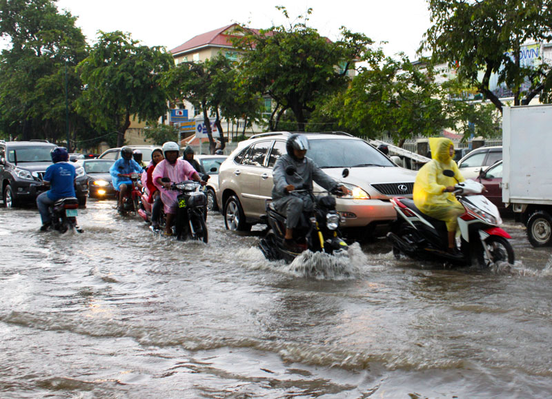 Motorists drive along a flooded stretch of Norodom Boulevard following torrential rains Tuesday afternoon. (Holly Robertson/The Cambodia Daily)