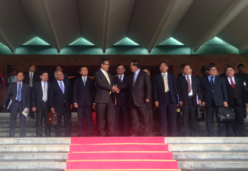 Opposition leader Sam Rainsy, left center, shakes hands with Prime Minister Hun Sen after the parties finalized an agreement Tuesday to end the country's nearly yearlong political deadlock. (Alex Willemyns/The Cambodia Daily)