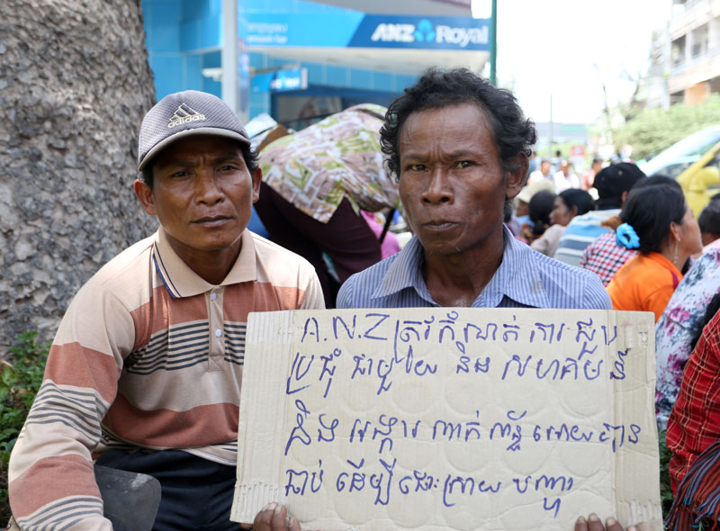 A villager holds up a sign reading 'ANZ must schedule a meeting immediately with the community and involved NGOs to find a solution' during a protest outside ANZ Royal's Phnom Penh headquarters on Thursday. (Siv Channa/The Cambodia Daily)