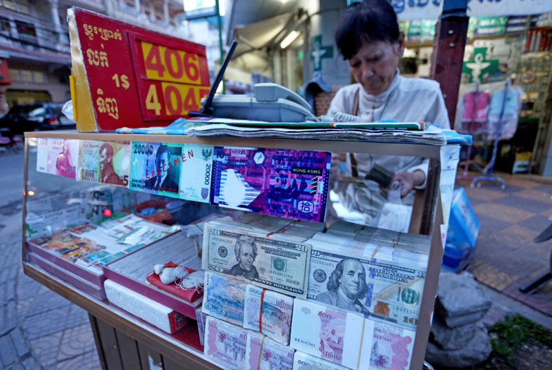 Khut Phany, 57, closes her money exchange stall Thursday evening on Street 284. (Siv Channa/The Cambodia Daily)