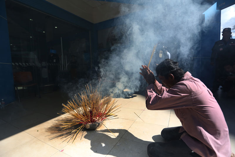 A man prays in front of the Phnom Penh headquarters of ANZ Royal Bank on Tuesday to lay a curse on the company. (Siv Channa/The Cambodia Daily)