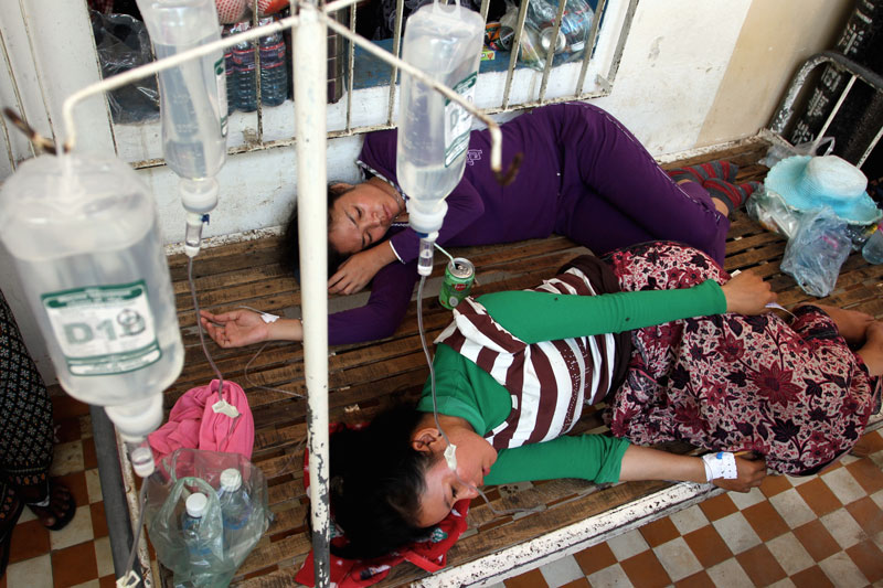 Two garment workers who were injured Tuesday when a floor collapsed at the Nishiku Enterprise factory in Takeo province lie outside Bati District Referral Hospital. (Siv Channa/The Cambodia Daily)