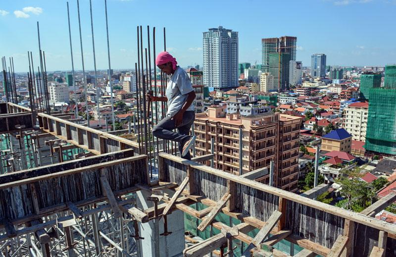 Construction worker Phal Roeun, 32, makes his way along a wooden frame atop a condominium construction site on Street 352 in Phnom Penh's Chamkar Mon district. (Alex Consiglio/The Cambodia Daily)