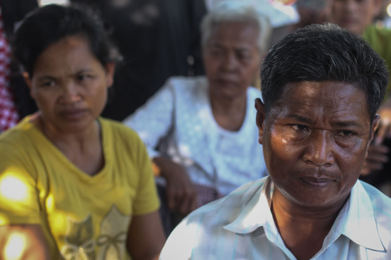 Seng Sna, 50, sits with other residents of the eviction-threatened Boeng Chhuk village in Phnom Penh's Russei Keo district Wednesday afternoon. (Chris Mueller/The Cambodia Daily)