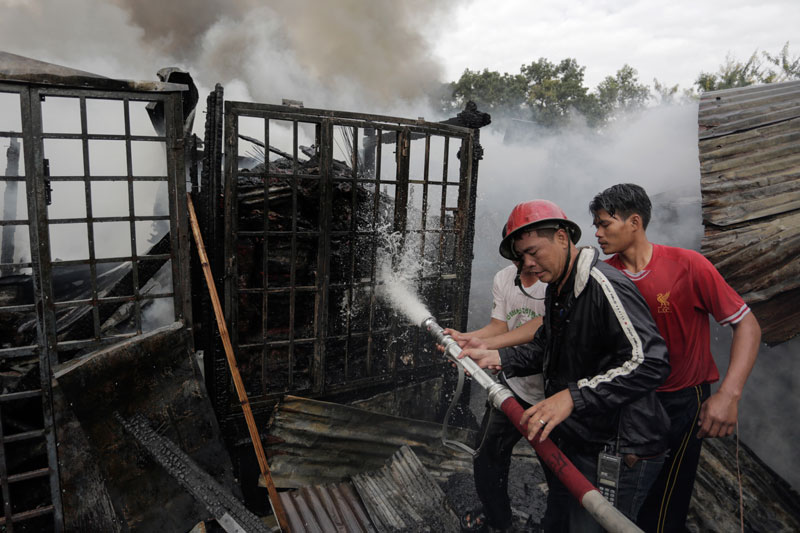 Vendors help a firefighter battle a blaze at Phnom Penh's Phsar Chas on Monday morning. (Siv Channa/The Cambodia Daily)