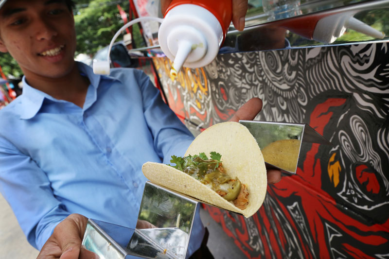 A man holds a taco on a platter as an Anabella's Hot Tacos vendor puts on green chili sauce. (Aria Danaparamita/The Cambodia Daily)