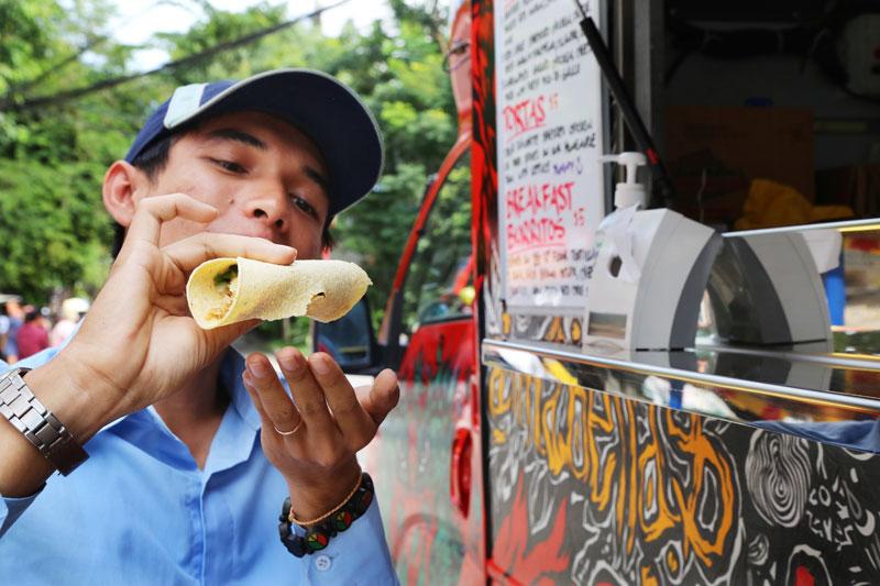 A man holds a taco next to Anabella's Tacos truck. (Aria Danaparamita/The Cambodia Daily)