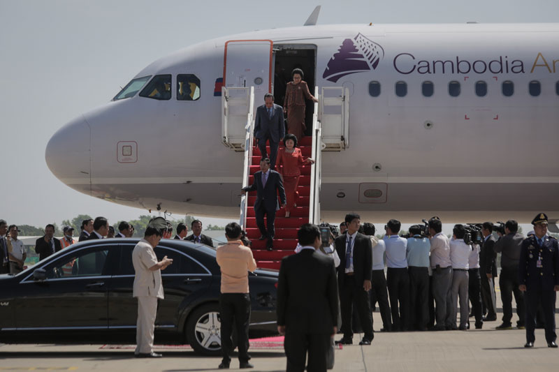 Prime Minister Hun Sen and his wife, Bun Rany, disembark from an airplane at Phnom Penh International Airport on Monday after returning from an official visit to Seoul. (Siv Channa/The Cambodia Daily)