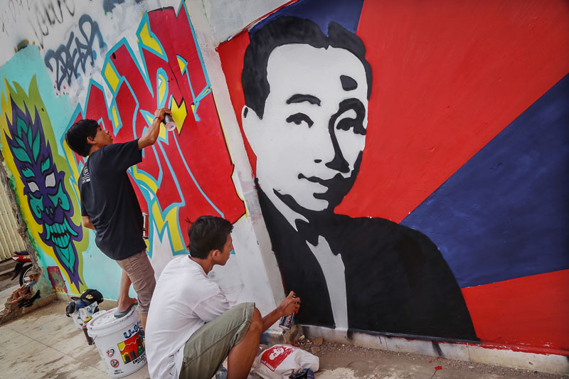 Ra Small, left, and Koy work on their street art pieces in Boeng Kak in November. (Aria Danaparamita/The Cambodia Daily)