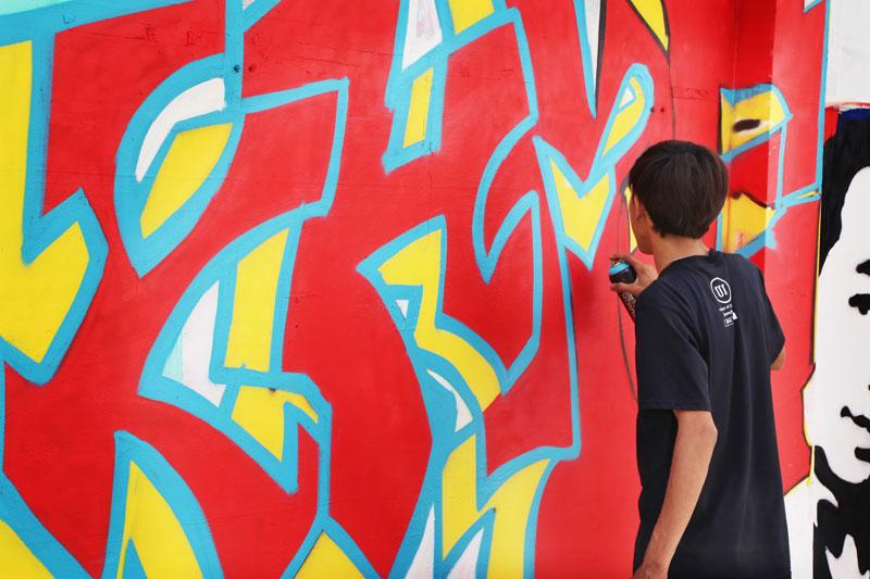 Ra Small works on his graffiti in Boeng Kak in November. (Aria Danaparamita/The Cambodia Daily)