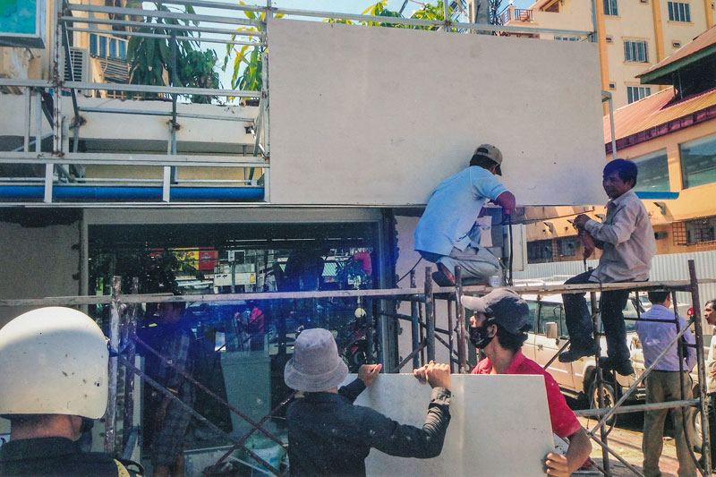 Construction workers erect a signboard earlier this year above VC Optics on Monivong Boulevard in Phnom Penh. (Meas Sophal)
