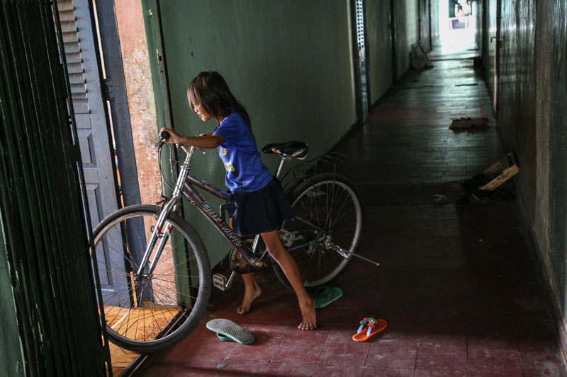 A girl walks a bicycle into an apartment at the White Building in Phnom Penh last year. (Aria Danaparamita/The Cambodia Daily)