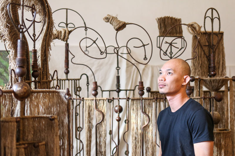 Thang Sothea stands among his sculptures from the 'Manu' series. (Alicia Guthert/The Plantation)