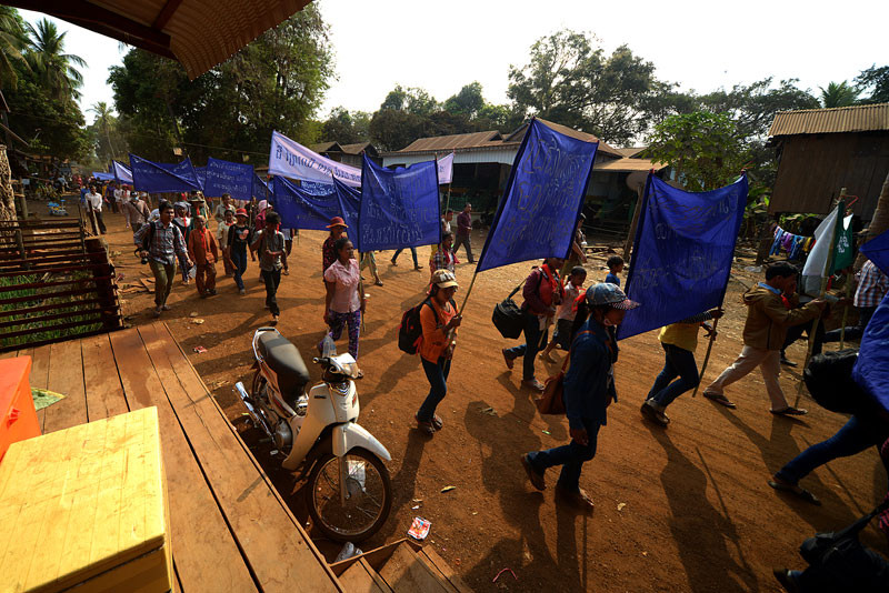 Villagers in Stung Treng province who oppose the construction of the Lower Sesan 2 dam march on Saturday to a shrine where a powerful local spirit is believed to live, in advance of a ceremony they held to curse the officials and businessmen behind the project. (Matt Walker)