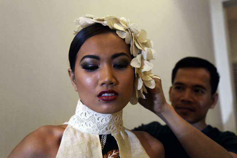 Pich Thavy adjusts a head piece on a model during rehearsals at The Plantation hotel on Wednesday. (Aria Danaparamita/The Cambodia Daily)