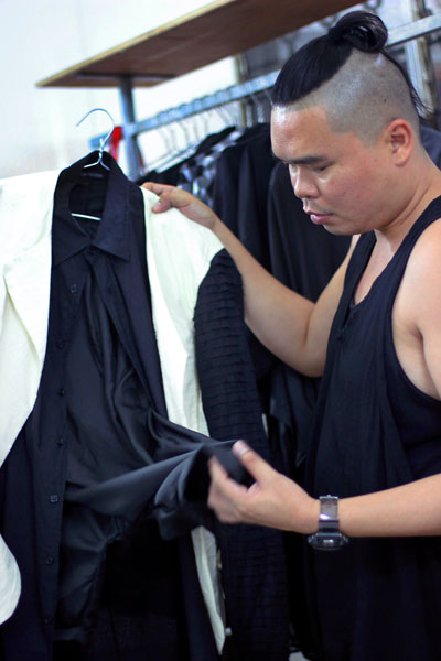 Don Protasio handles a garment in his collection at his showroom on Wednesday. (Aria Danaparamita/The Cambodia Daily)