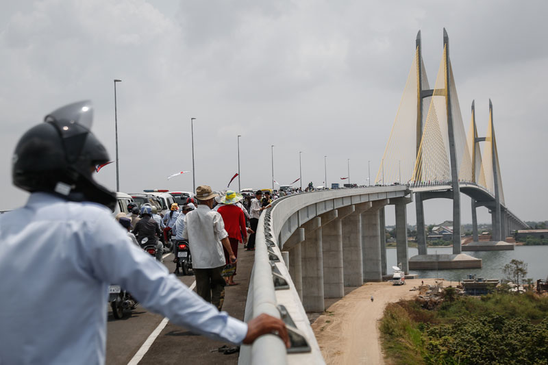 A motorist inspects the Tsubasa Bridge shortly after its opening Monday. (Siv Channa/The Cambodia Daily)