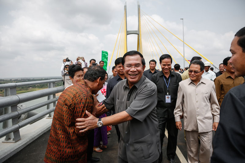 Prime Minister Hun Sen greets supporters Monday after inaugurating the $127 million Tsubasa Bridge, which links Kandal and Prey Veng provinces across the Mekong River. (Siv Channa/The Cambodia Daily)