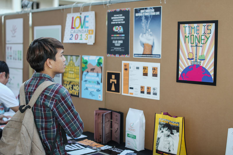 A visitor peruses the M'lo collective's exhibition at the Institute for Foreign Languages in Phnom Penh last month. (M'lo collective)