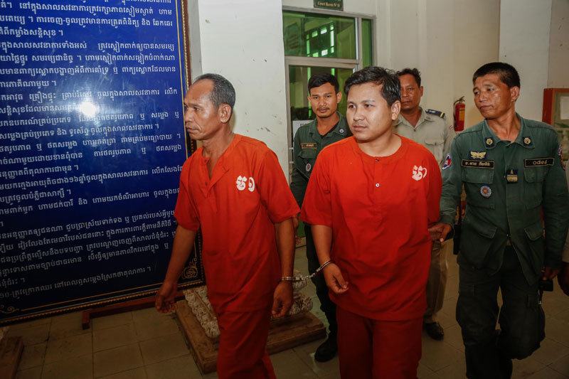 Men convicted of plotting to overthrow the government as part of the Khmer National Liberation Front are escorted out of the Appeal Court in Phnom Penh on Monday. (Siv Channa/The Cambodia Daily)