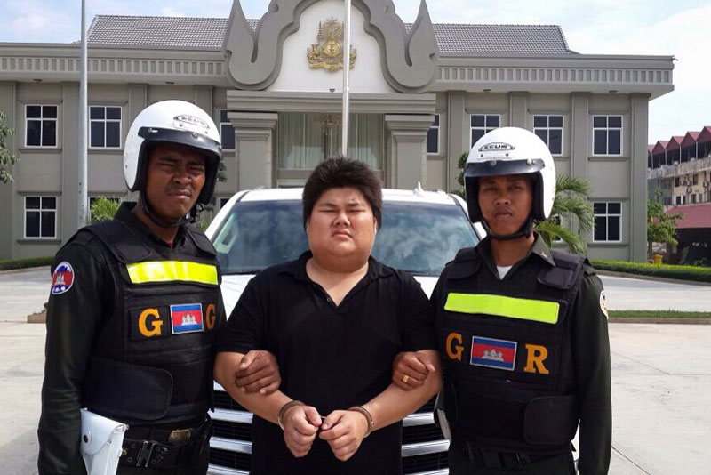 Duong Udomchorvin stands outside the Phnom Penh military police headquarters Tuesday after being arrested for slapping Try Daluch at a tattoo parlor the night before, in a photograph supplied by military police.