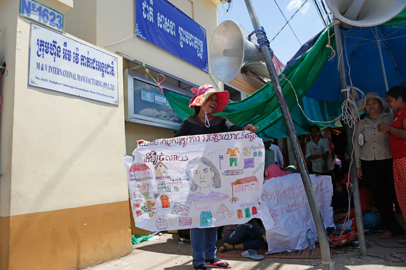 A garment worker holds up a sign at a protest outside the M&V International Manufacturing factory in Phnom Penh's Meanchey district on Wednesday. (Siv Channa/The Cambodia Daily)