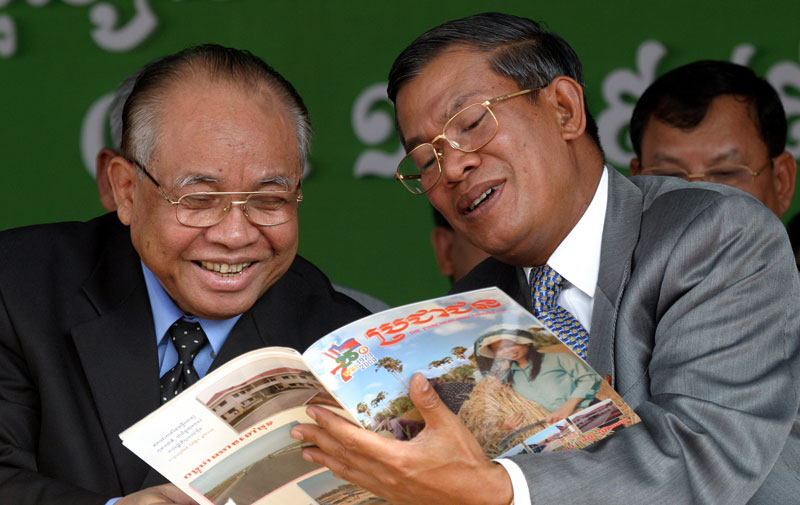 Chea Sim, left, and Prime Minister Hun Sen read a magazine on January 7, 2004, during a ceremony marking the 25th anniversary of the fall of the Khmer Rouge in 1979. (Reuters)