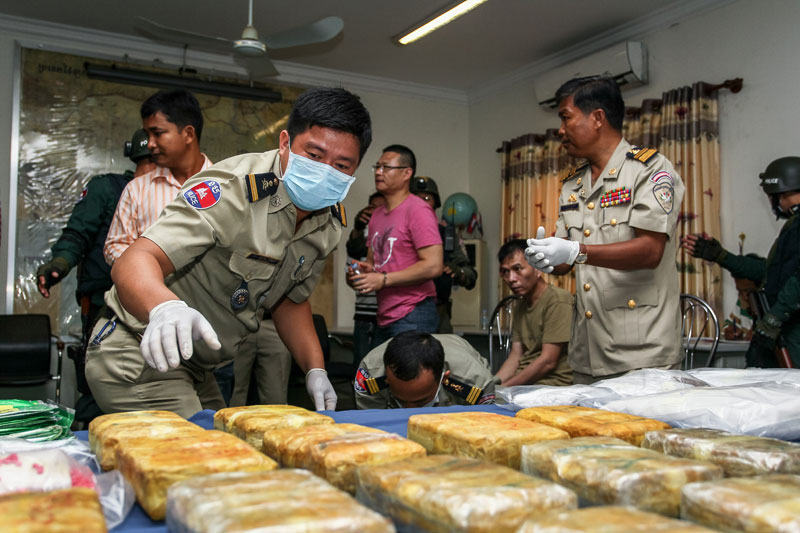 Police officers from the Interior Ministry's anti-drug department place packages of methamphetamine on a table ahead of a press conference at the National Police headquarters in Phnom Penh on Saturday. (Masayori Ishikawa)