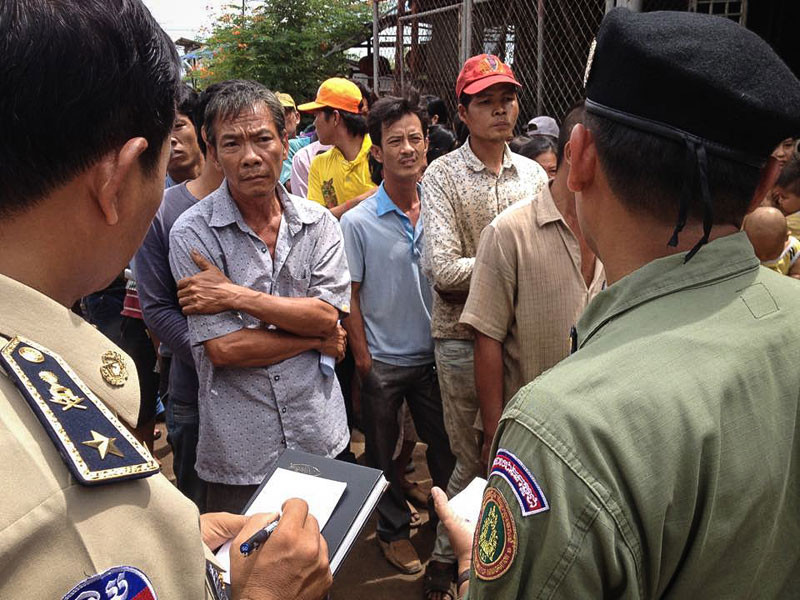 Immigration police take down information about suspected illegal immigrants from Vietnam at a Phnom Penh scrapyard last year. (Matt Blomberg/The Cambodia Daily)