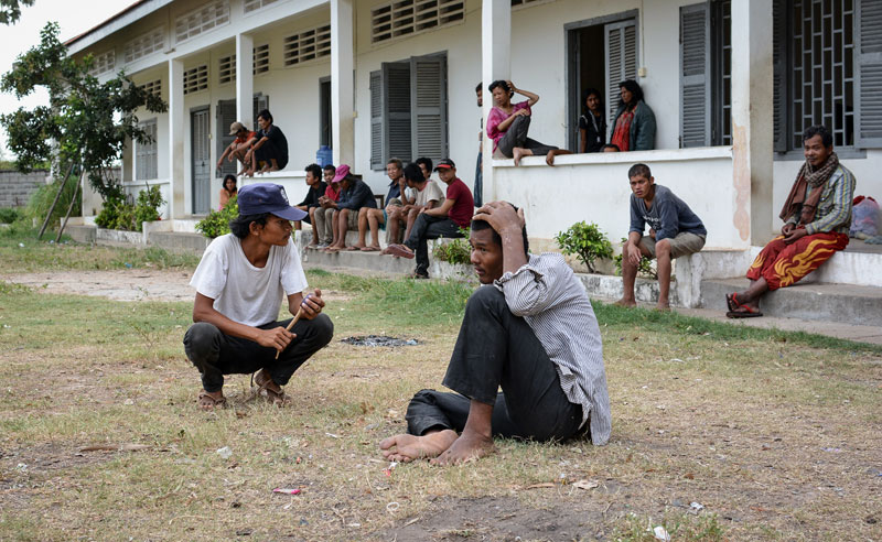 A guard, left, squats among detainees at the Pur Senchey Vocational Training Center in Phnom Penh on Tuesday. (Alex Consiglio/The Cambodia Daily)
