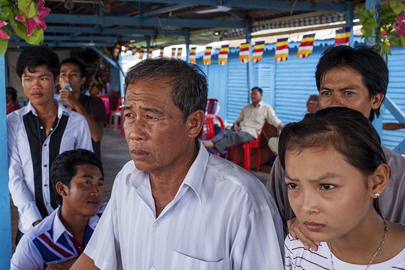 Mr Heang peers out from one of the platforms that make up his community in the floating villages on the Tonle Sap river in Kompong Chhnang City last week.
