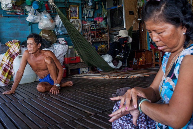 Veang Yang Tourng, left, sits with his family in his small floating home, a day after they were relocated last week.