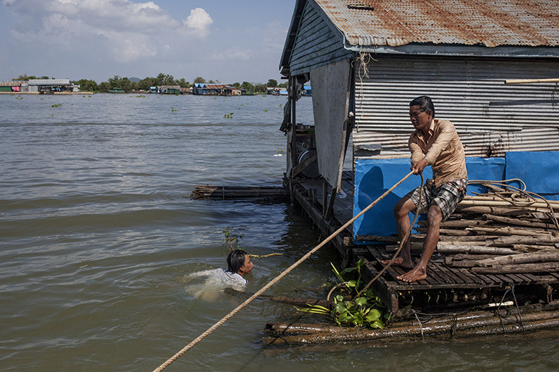 A young man moors his floating house to a neighboring house last week after moving it down the river.