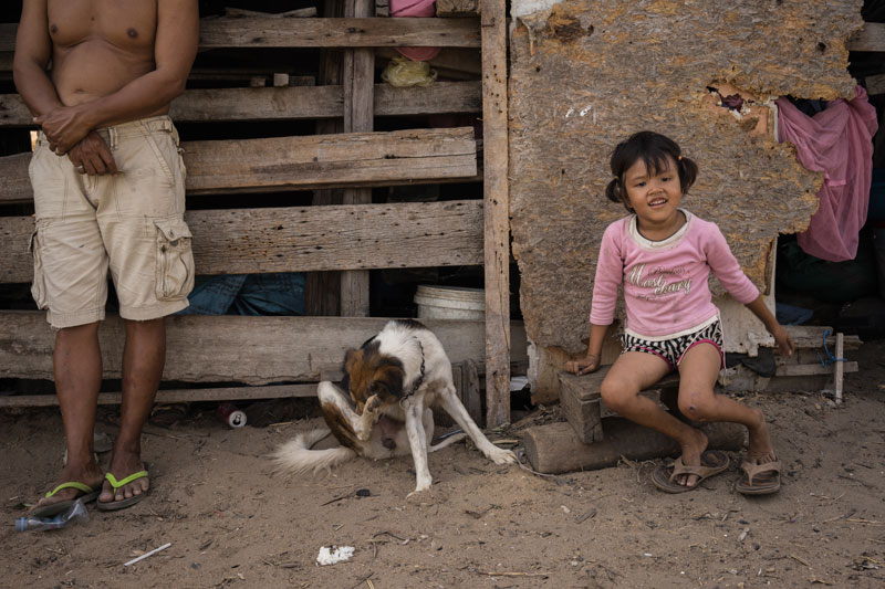 Mr Chantha and his 7-year-old daughter Vanau outside their house in March (Ben Woods/The Cambodia Daily)