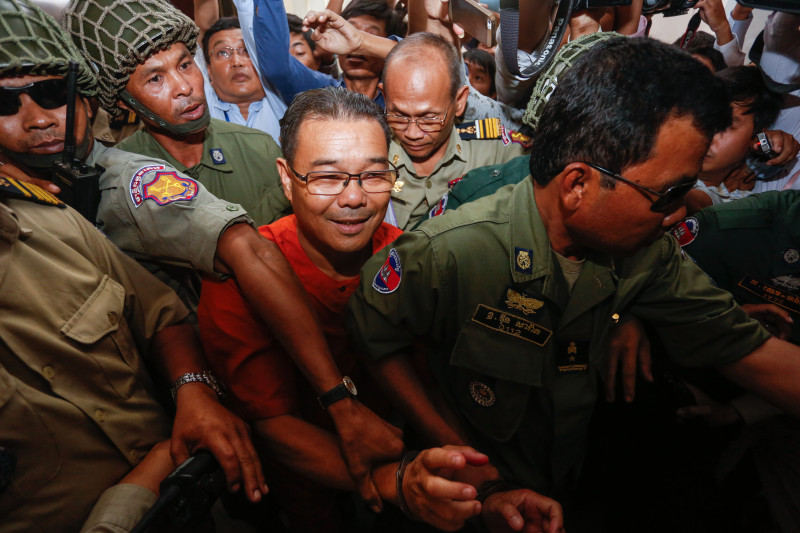 Opposition senator Hong Sok Hour is escorted from the Phnom Penh Municipal Court on Friday after the first day of his trial on incitement and forgery charges. (Siv Channa/The Cambodia Daily)
