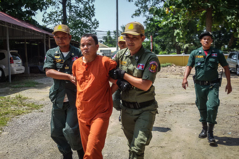 Unlicensed medic Yem Chrin is escorted from the Battambang Provincial Court yesterday after the first day of his trial over a mass outbreak of HIV. (Khy Sovuthy)